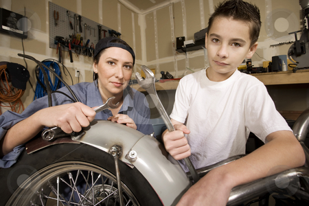 Hispanic woman and boy in garage stock photo, Hispanic mother and son working on motorcycle in garage by Scott Griessel