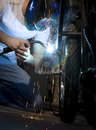 Welder working on motorcycle stock photo, Welder working on the metal fork of a motorcycle by Scott Griessel