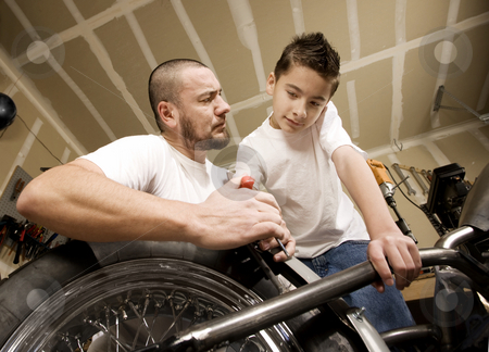Hispanic father and son in garage stock photo, Hispanic father and son working on motorcycle in garage by Scott Griessel
