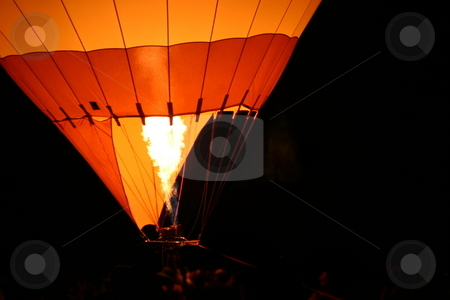 Hot Air Baloon stock photo, Hot air balloon with flames from the burner at night to show a glow. by Henrik Lehnerer