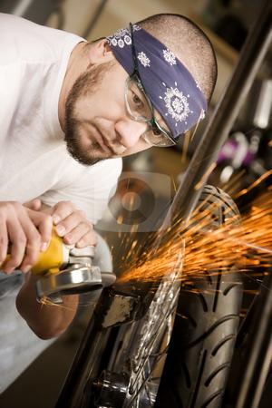 Hispaninc man using grinder on motorcycle stock photo, Hispaninc man using grinder tool on the front fork of motorcycle by Scott Griessel
