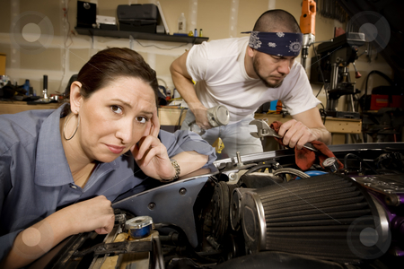 Bored woman with mechanic in background stock photo, Bored woman leaning on car with male mechanic ignoring her in background by Scott Griessel