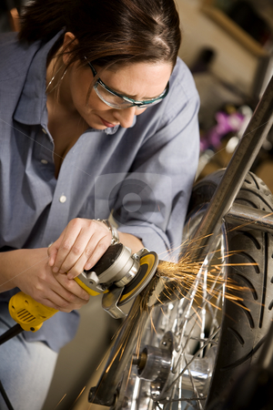 Hispaninc womman using grinder on motorcycle stock photo, Hispanic womman using grinder tool on the front fork of motorcycle by Scott Griessel