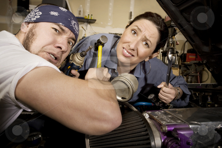 Hapless mechanics stock photo, Hapless mechanics working on car with all the wrong tools by Scott Griessel