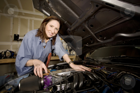 Female Hispanic Mechanic stock photo, Female Hispanic mechanic working on a car engine by Scott Griessel