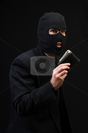 Stealing Company Money stock photo, Concept image of a thief wearing a black business suit and holding a wallet, shot against a dark background by Richard Nelson