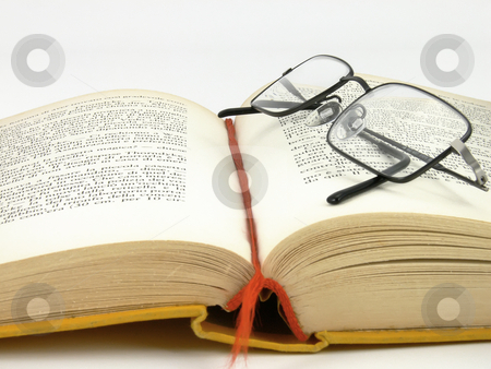 Book and glasses stock photo, Opened yellow book with glasses on pages by Matteo Malavasi