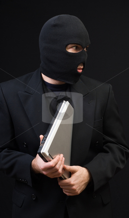 Stealing Office Equipment stock photo, A business thief wearing a black balaclava is stealing a laptop computer by Richard Nelson
