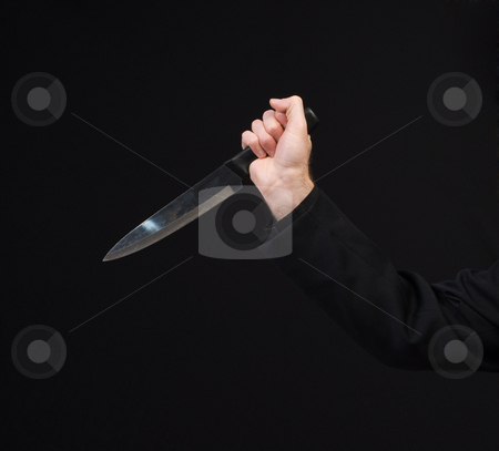 Stabbing stock photo, Closeup view of a hand holding a large kitchen knife in a stabbing motion by Richard Nelson