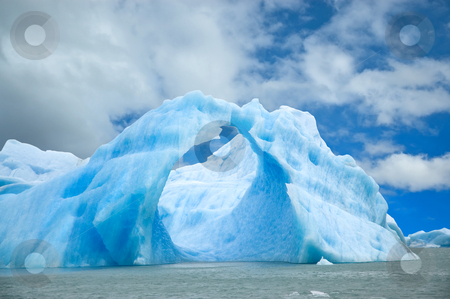 Iceberg floating in the water. stock photo, Iceberg floating in the water forming an arch. by Pablo Caridad