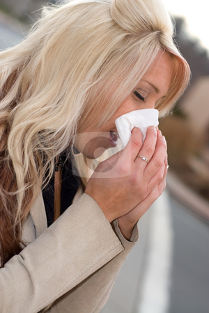 Blowing Her Nose stock photo, This young woman sneezing into a tissue either has a cold or really bad allergies. by Todd Arena