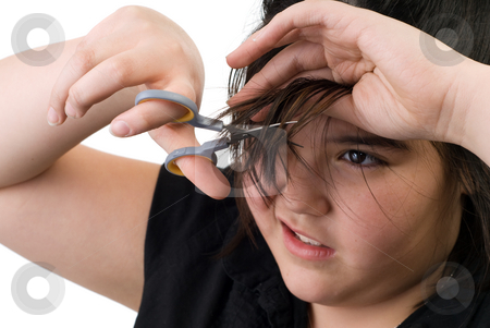 Hair Cut stock photo, A young girl trying to cut her own hair with a pair of scissors, isolated against a white background by Richard Nelson