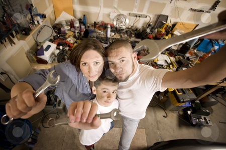 Do-It-Yourself family with wrenches stock photo, Funny Hispanic family in garage with crescent wrenches by Scott Griessel