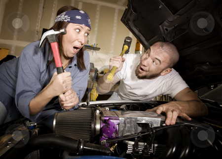 Hapless mechanics stock photo, Hapless mechanics working on car engine with hammers by Scott Griessel