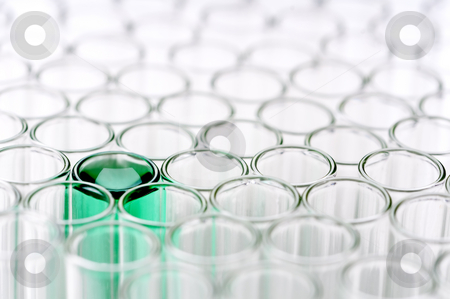 Shallow focus close-up of empty glass test tubes, one with a gre stock photo, Shallow focus close-up of empty glass test tubes, one with a green liquid by Vince Clements