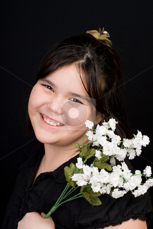 Cute Child Portrait stock photo, Portrait of a cute girl holding some white flowers, shot against a dark background by Richard Nelson