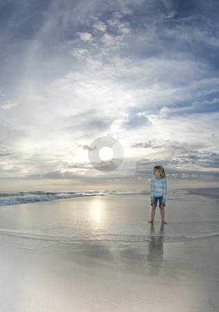 Child in Beach Surf stock photo, A child watches the surf flow in while the setting sun reflects off the water and the clouds glow on the horizon by A Cotton Photo