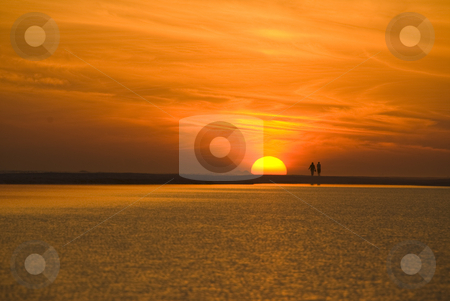Couple Walk in Sunset stock photo, A couple walks along the beach during sunset with a spectacularly colorful sky by A Cotton Photo