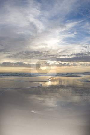 Beach Surf 2 stock photo, The setting sun reflects off the water as the surf flows in and the clouds glow on the horizon by A Cotton Photo