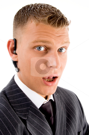 Handsome professional guy wearing bluetooth with facial expressi stock photo, Handsome professional guy wearing bluetooth with facial expressions against white background by Imagery Majestic