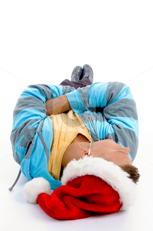 Laying man with christmas hat and ear phones stock photo, Laying man with christmas hat and ear phones on an isolated white background by Imagery Majestic