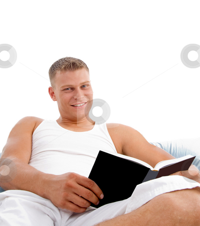 Bedtime reading in bed a book stock photo, Man enjoying reading in bed on white background by Imagery Majestic