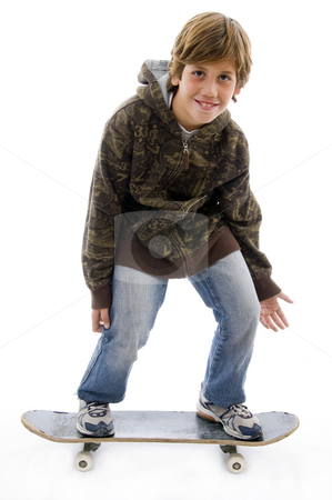 Front view of smiling child standing on skateboard  stock photo, Front view of smiling child standing on skateboard on an isolated background by Imagery Majestic