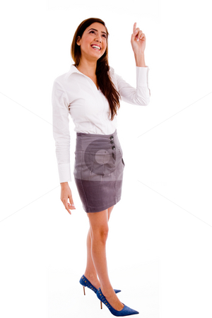Standing woman pointing up stock photo, Side pose of standing manager pointing up against white background by Imagery Majestic
