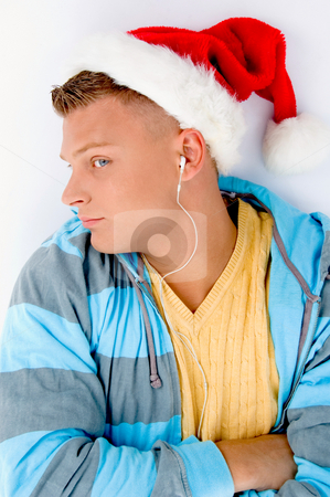 Man wearing christmas hat and listening to music stock photo, Man wearing christmas hat and listening to music on an isolated white background by Imagery Majestic