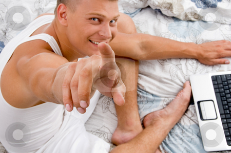 Pointing male looking at camera stock photo, Pointing male looking at camera in bed by Imagery Majestic