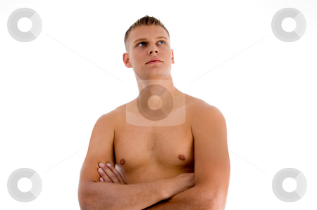Muscular man with crossed arms looking upward stock photo, Muscular man with crossed arms looking upward on an isolated background by Imagery Majestic