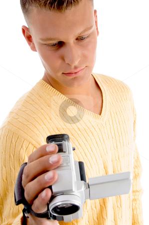 Male operating video camera stock photo, Male operating video camera with white background by Imagery Majestic