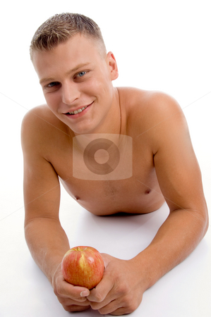 Laying fit guy with apple stock photo, Laying fit guy with apple on an isolated white background by Imagery Majestic