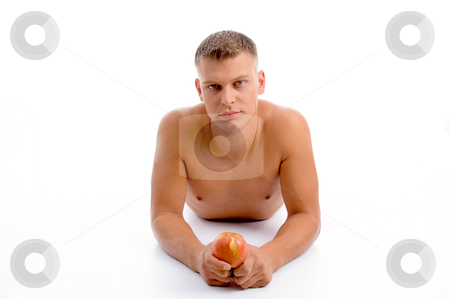 Laying fit man with apple stock photo, Laying fit man with apple against white background by Imagery Majestic