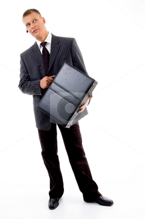 Full pose of young executive holding leather bag stock photo, Full pose of young executive holding leather bag against white background by Imagery Majestic