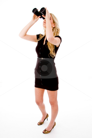 Side view of young woman looking through binocular stock photo, Side view of young woman looking through binocular on an isolated white background by Imagery Majestic
