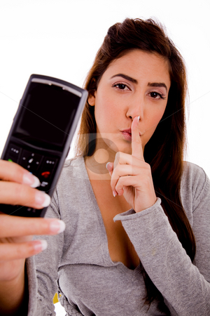 Woman with cell phone instructing to be silent stock photo, Portrait of woman with cell phone instructing to be silent with white background by Imagery Majestic