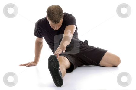 Man stretching his legs stock photo, Man stretching his legs against white background by Imagery Majestic