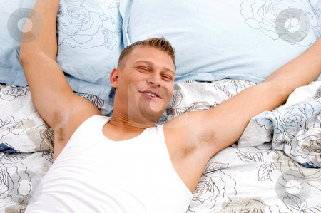 Man stretching his arms in bed stock photo, Relaxing man stretching his arms in bed by Imagery Majestic