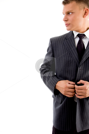Young ceo tucking his coat button stock photo, Young ceo tucking his coat against white background by Imagery Majestic