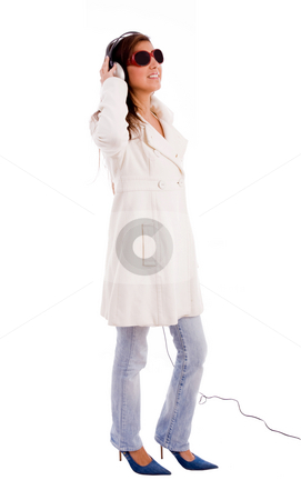 Side pose of standing model listening music stock photo, Side pose of standing model listening music with white background by Imagery Majestic