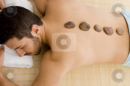 High angle view of male relaxing for hot stone treatment stock photo, High angle view of male relaxing for hot stone treatment by Imagery Majestic