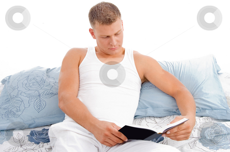 Reading book - male reading in bed relaxing stock photo, Handsome male reading book in bed with white background by Imagery Majestic