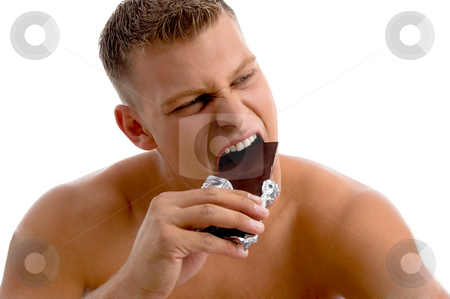 Muscular guy eating chocolate stock photo, Muscular guy eating chocolate with white background by Imagery Majestic