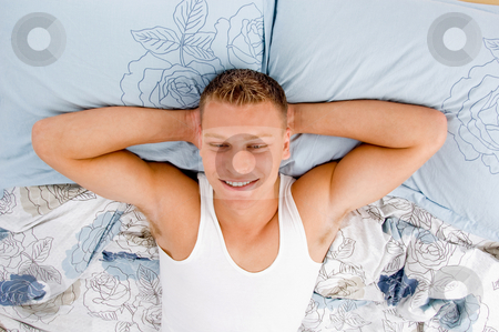 Vacation - male relaxing on his bed stock photo, Tired young male relaxing on his bed in bed by Imagery Majestic