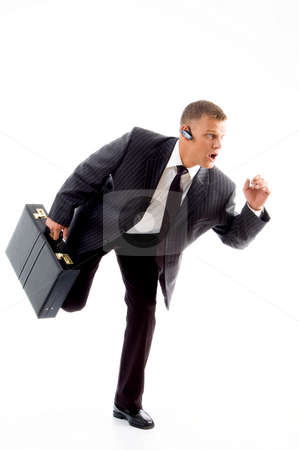 Young accountant holding bag in walking posture stock photo, Young accountant holding bag in walking posture on an isolated white background by Imagery Majestic