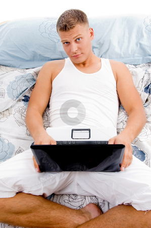 Man working on laptop in bed stock photo, Man working on laptop in bed by Imagery Majestic