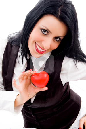 Woman smiling and holding a small red heart stock photo, Woman smiling and holding a small red heart against white background by Imagery Majestic