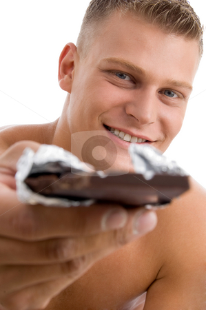 Muscular man offering chocolate stock photo, Muscular man offering chocolate on an isolated background by Imagery Majestic