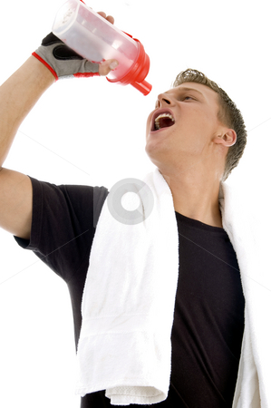 Man taking drink while exercise stock photo, Man taking drink while exercise on an isolated background by Imagery Majestic